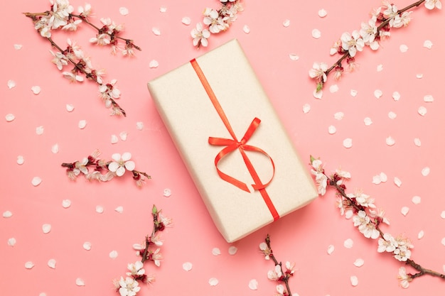Caixa surpresa de presente com raminhos de flores e pétalas em um fundo rosa