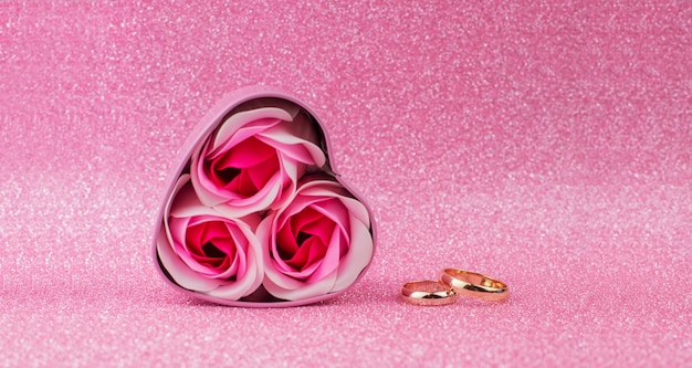 Caixa surpresa presente coração rosa com alianças de ouro com rosas em um fundo brilhante com bokeh para o dia dos namorados