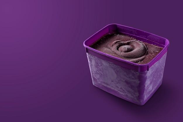 Caixa tigela roxa brasileira de sorvete de frutas vermelhas e congeladas. isolado em fundo roxo. vista frontal do menu de verão