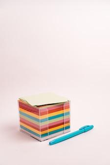 Caixa transparente de adesivos coloridos e uma caneta azul em um branco