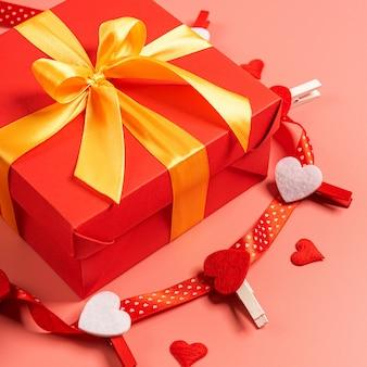 Caixa vermelha amarrada com uma fita de ouro. a fita está amarrada em uma caixa na forma de um lindo laço.