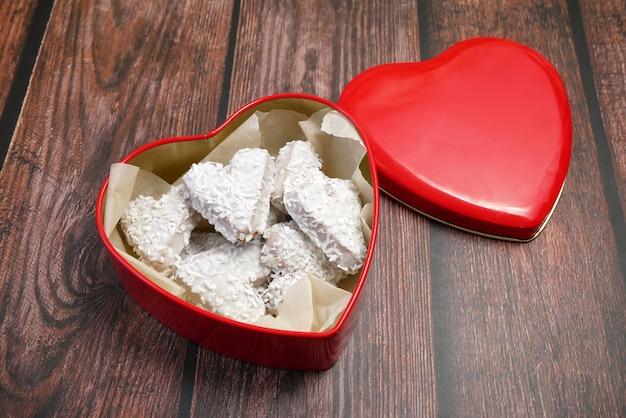 Caixa vermelha com formato de coração e biscoitos saborosos com coco, doce conceito de dia dos namorados