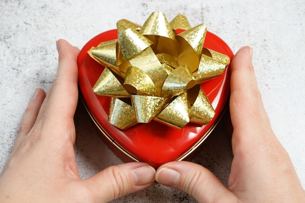 Caixa vermelha com formato de coração e laço