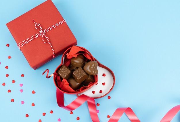 Caixa vermelha em forma de coração aberto cheia de chocolates