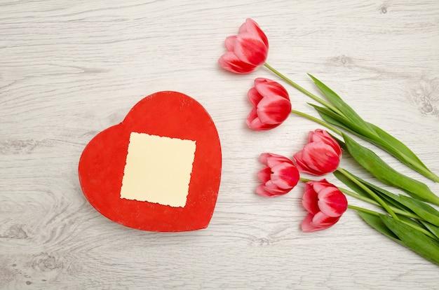 Caixa vermelha em forma de coração cartão limpo, tulipas cor de rosa em uma luz de madeira. vista superior, copyspace