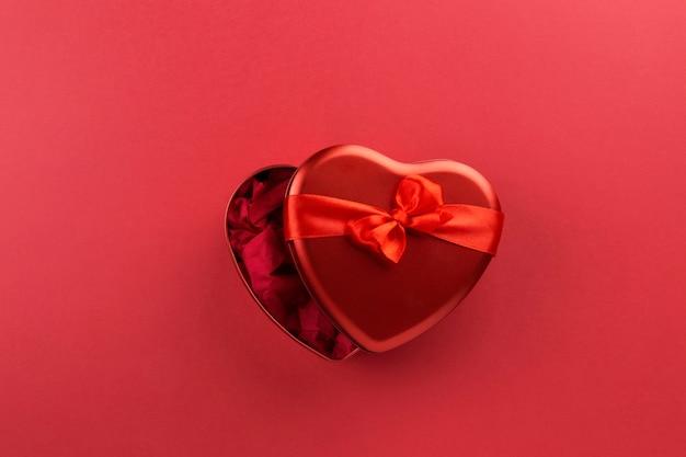 Caixa vermelha em forma de coração com fita em fundo vermelho