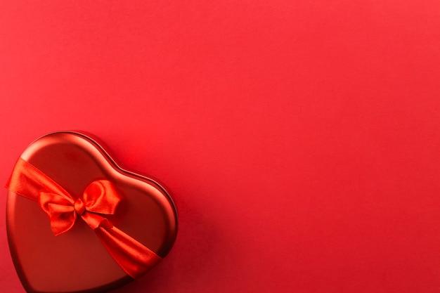 Caixa vermelha em forma de coração com fita sobre fundo vermelho. vista superior, espaço de cópia