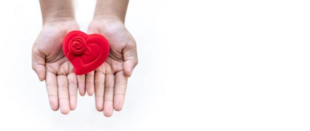 Caixa vermelha em forma de coração na mão da criança, conceito de amor, cuidados de saúde, conceito de doação e seguro familiar, dia mundial do coração, dia mundial da saúde, conceito