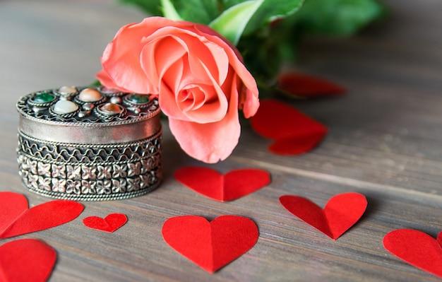 Caixão antik de prata com flor e corações de papel vermelhos.