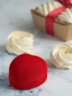 Caixão vermelho para um anel ou um presente em uma mesa cinza. marshmallow caseiro (zéfiro) em cima da mesa. doces caseiros.