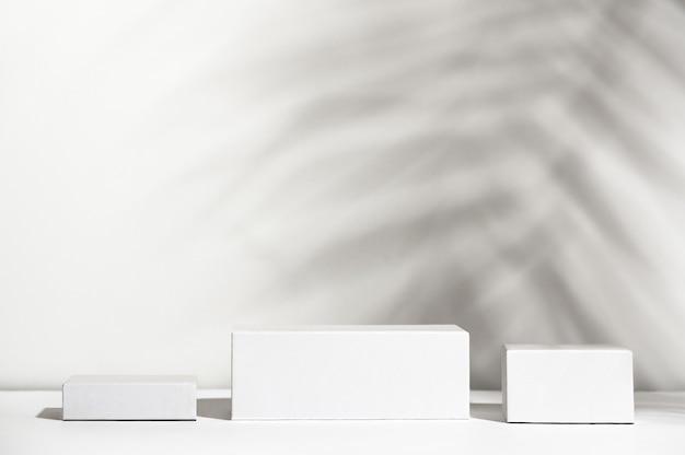 Caixas brancas de diferentes formas em pé no fundo da sombra. vitrine vazia sem marca. vitrine de produtos cosméticos. anúncio do produto. design de estilo de maquete. conceito de cosmetologia e beleza.