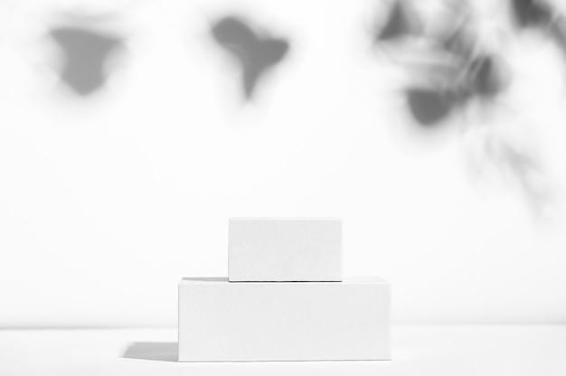 Caixas brancas vazias de diferentes formas em um cenário claro com sombra. vitrine de produtos cosméticos. anúncio do produto. amostra de exibição. coloque o estilo mockup. cosmetologia e conceito de beleza