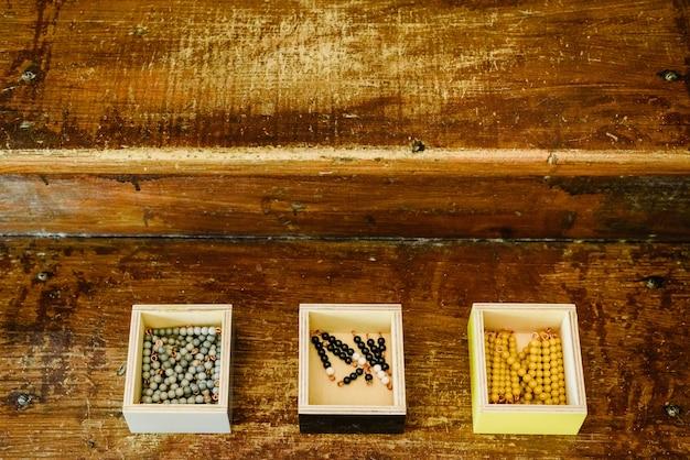 Caixas com contas para aprender a contar em uma sala de aula montessori em madeira envelhecida.