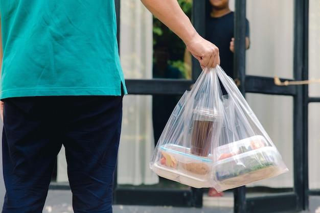Caixas de alimentos em sacos plásticos entregues ao cliente em casa pelo entregador