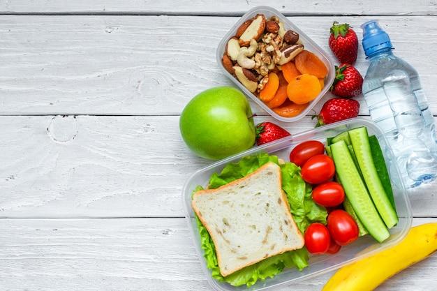 Caixas de almoço escolar com sanduíche e legumes frescos, garrafa de água, nozes e frutas