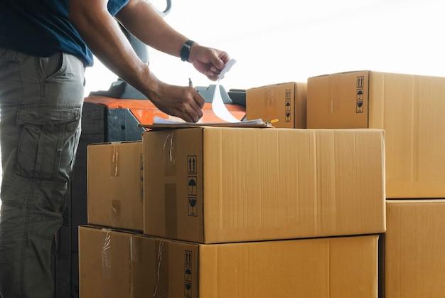 Caixas de carga enviadas. trabalhador, escrevendo na área de transferência, fazendo caixas de carga de gerenciamento de estoque.