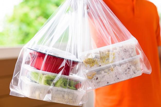 Caixas de comida asiática em sacos de plástico entregues ao cliente em casa pelo entregador de uniforme laranja