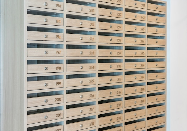 Caixas de correio cheias de folhetos e cartas, caixas de correio e bloqueio em linhas na entrada.