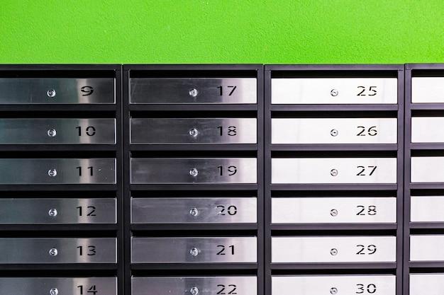 Caixas de correio em um prédio de apartamentos, feitas de aço inoxidável, em uma parede verde