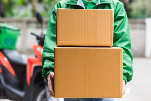 Caixas de encomendas de entrega em domicílio pelo entregador de correio com uniforme verde de jaqueta com moto borrão. compras online por aplicativo móvel. conceito de serviço de entrega de casa. novo covid19 normal.