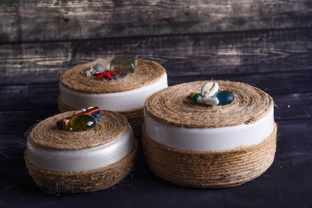Caixas de joias em uma parede de madeira. caixas redondas decoradas com atributos marinhos