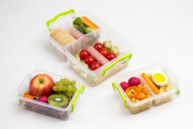 Caixas de merenda escolar com frutas, nozes e vegetais na mesa