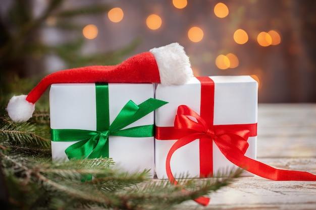 Caixas de natal branco ou presentes com chapéu de papai noel na mesa de madeira branca.