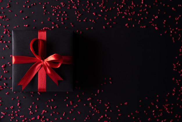 Caixas de natal pretas com fita vermelha em fundo preto.