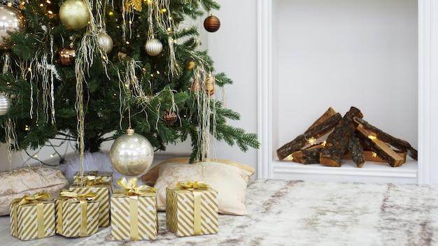 Caixas de ouro com presentes embaixo da árvore de natal