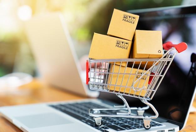 Caixas de pacote no carrinho com o computador portátil para o conceito de compras on-line