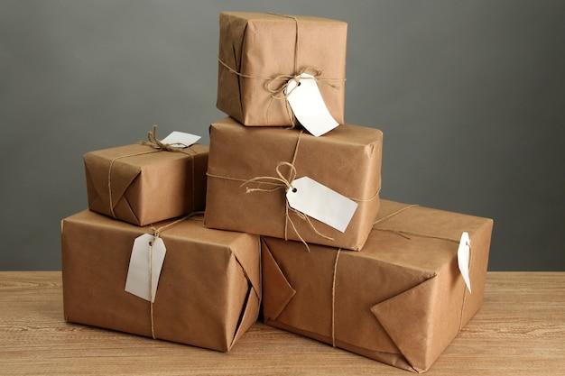 Caixas de pacotes com papel kraft, em mesa de madeira em fundo cinza