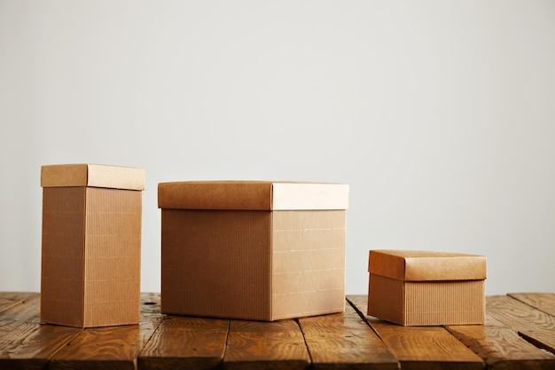 Caixas de papel bege de tamanhos e formatos diferentes em uma mesa de madeira em um estúdio com paredes brancas