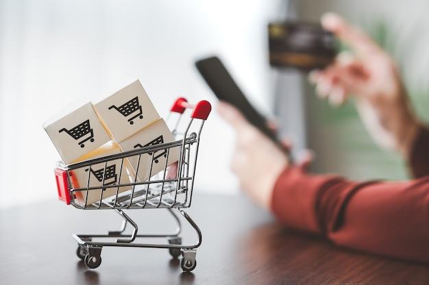 Caixas de papel com logotipo de carrinho de compras em um carrinho com a mão segurando o smartphone e o cartão de crédito
