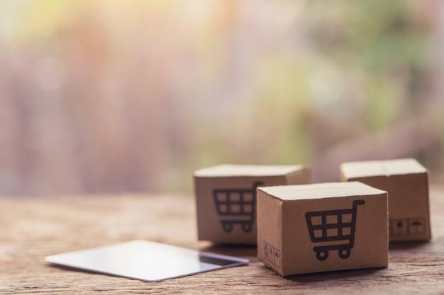 Caixas de papel com um logotipo de carrinho de compras e cartão de crédito em cima da mesa de madeira.