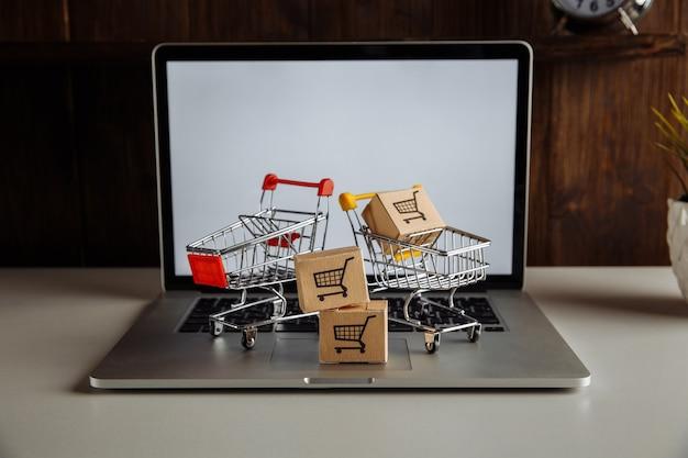 Caixas de papel e carrinhos em um teclado de laptop. conceito de compras, comércio eletrônico e entrega online.