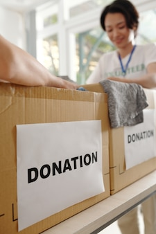Caixas de papelão cheias de roupas na mesa do centro de caridade, foco seletivo