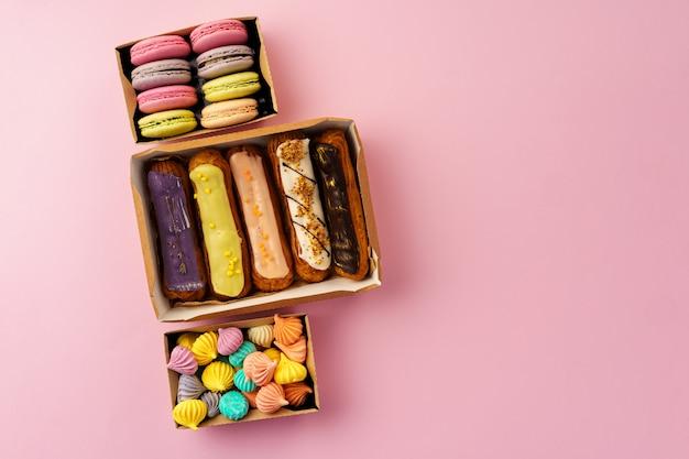Caixas de papelão com bolos eclair e biscoitos na superfície rosa
