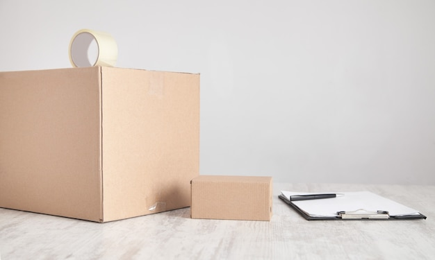 Caixas de papelão com prancheta na mesa produtos, comércio, varejo, entrega