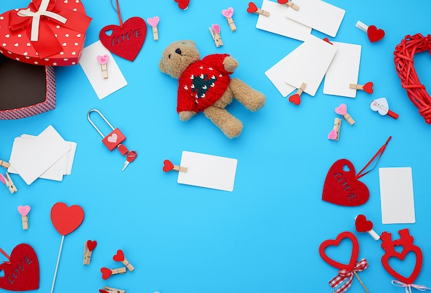 Caixas de papelão em forma de coração, um pequeno ursinho de pelúcia, cartões de visita em branco brancos com prendedores de roupa sobre um fundo azul
