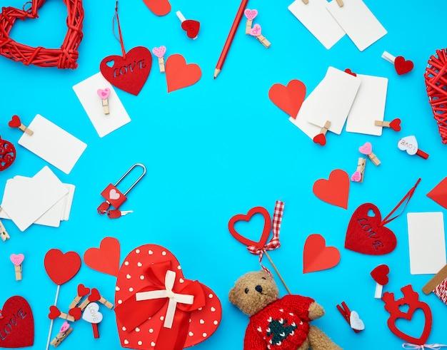 Caixas de papelão em forma de coração, um pequeno urso de pelúcia, cartões de visita em branco brancos com prendedores de roupa