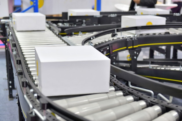 Caixas de papelão na correia transportadora no armazém de distribuição. conceito de sistema de transporte de peças.