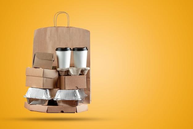 Caixas de pizza e saco de papel de entrega de comida com uma xícara de café descartável e uma caixa de wok em um fundo amarelo
