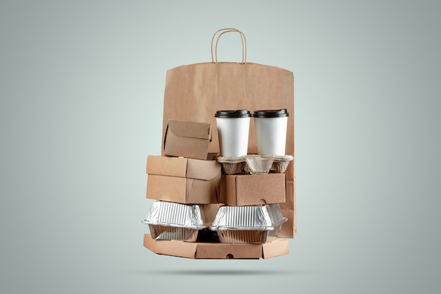 Caixas de pizza e saco de papel de entrega de comida com uma xícara de café descartável e uma caixa de wok em um fundo azul