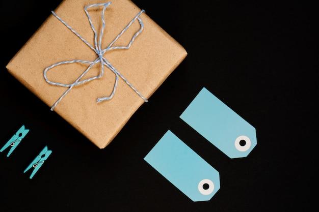 Caixas de presente artesanais embrulhadas em papel ofício com etiqueta de cartão de papel azul, corda e prendedores de roupa de madeira para decoração.