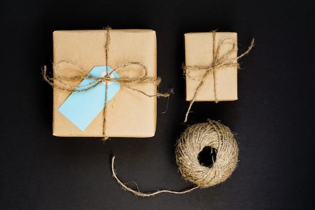 Caixas de presente artesanais embrulhadas em papel ofício com etiqueta de cartão de papel azul e corda para decoração.