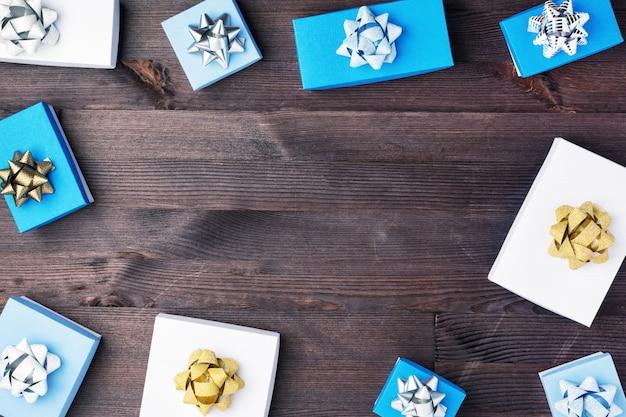 Caixas de presente azuis e brancas com laços decorativos são dispostas em um fundo escuro de madeira.