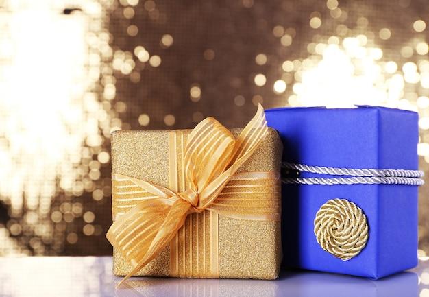Caixas de presente azuis e douradas na mesa em superfície brilhante