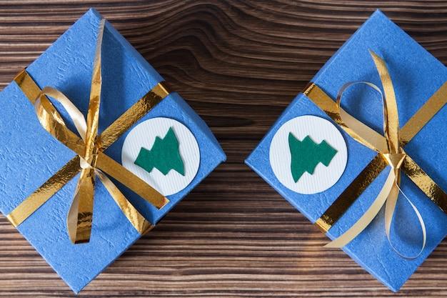 Caixas de presente azul com fitas douradas em um marrom de madeira para o natal e ano novo