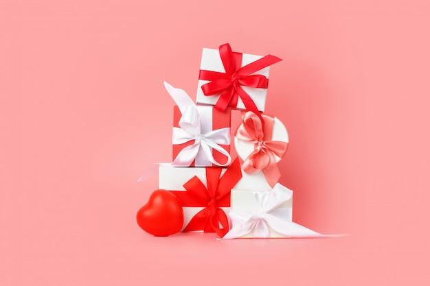 Caixas de presente branca com fitas de cetim vermelhas sobre um fundo rosa. presentes festivos para são valentim, dia internacional da mulher, casamento ou noivado.