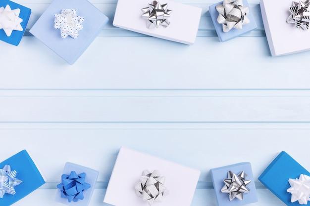Caixas de presente brancas e azuis decoradas com laços de prata.